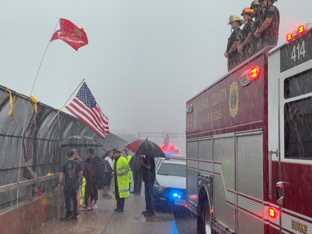 Fairfax firefighters and onlookers saluted the procession for a fallen soldier as the storm moved through Annandale.