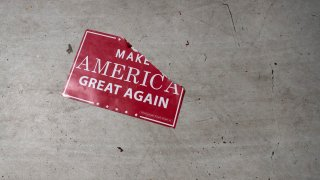 """a """"Make America Great Again"""" sign sits on the floor"""