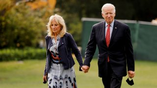 U.S. President Joe Biden and U.S. first lady Jill Biden walk after arriving in the Marine One helicopter on the South Lawn of the White House