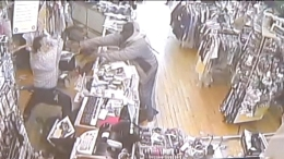 WATCH: Shop Owner Dodges Bullets, Fights Robbers with a Bat