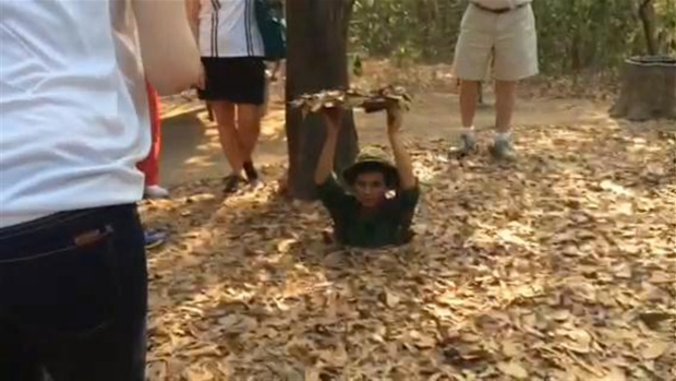 Guide Climbs into Viet Cong Tunnel